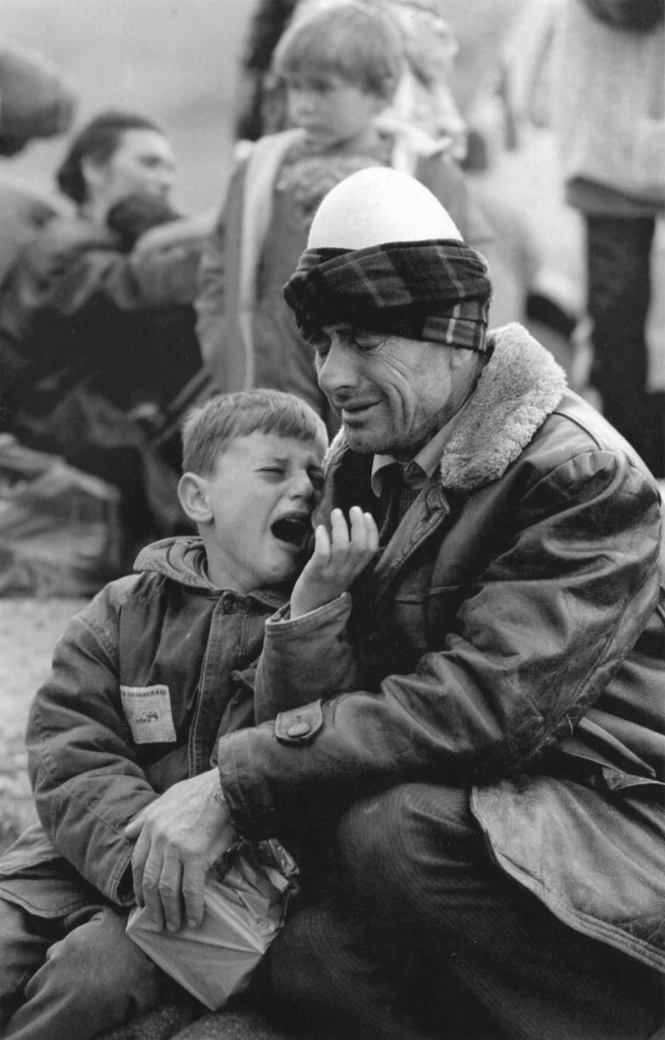 April 1999: Von der Flucht aus der alten Heimat zermürbt - ein Vater und sein weinender Sohn im albanischen Morina, unweit von Prizren.