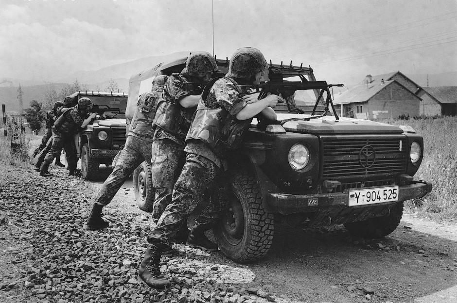 Juni 1999: Bundeswehrsoldaten suchen in Prizren hinter ihren Geländewagen Deckung und bringen ihre Gewehre in Anschlag.