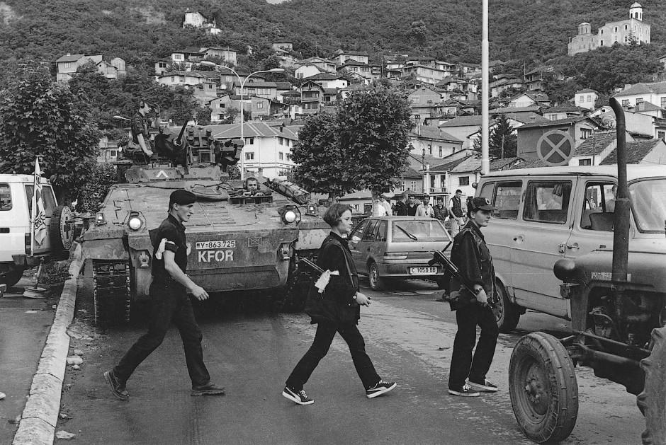Zwei Kämpferinnen der albanischen Untergrundarmee UCK überqueren mit ihren Kalaschnikow AK 47 in Prishtina eine Straße, während KFOR-Soldaten der Bundeswehr in ihrem Schützenpanzer Marder die Straße sichern.