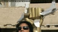 Gaddafi vor der Blech-Skulptur, die er vor seine Kaserne pflanzte: eine Faust, die ein amerikanisches Kampfflugzeug zerquetscht