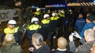 Polizisten stehen Demonstranten gegenüber, nachdem während einer Gemeindeversammlung die Planung eines Flüchtlingslagers für 1500 Personen bekannt gegeben wurde.