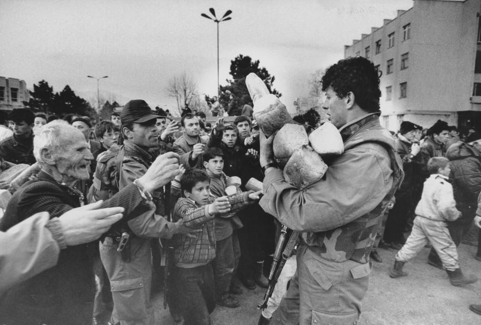 Ein Soldat verteilt im albanischen Auffanglager in Kukes Brot an Flüchtlinge aus dem Kosovo.