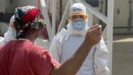 Helfer mit Ebola-Patient in einem Krankenhaus in Sierra Leone