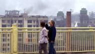 Zwei Chinesinnen blicken auf Industriegebiete der Großstadt Chongqing (8. Juni 2000)