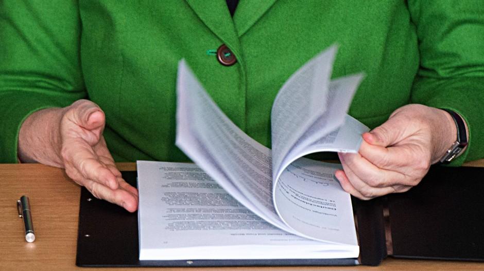 Angela Merkel blättert am Mittwoch durch den Koalitionsvertrag