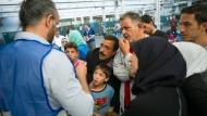 Tun was: Helfer versorgen Flüchtlinge in einer Erstaufnahmeeinrichtung mit Informationen.